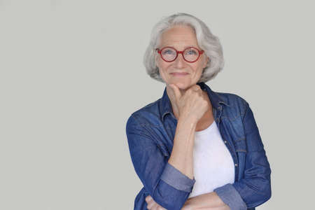 Portrait of senior woman wearing blue jeans shirt and red eyeglasses, isolated