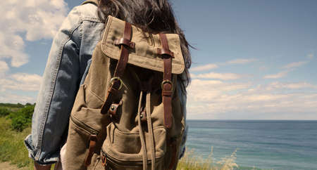 Closeup of backpack, woman standing in front of the sea