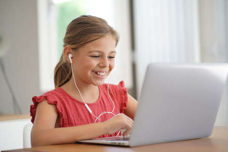 Young blond girl with red shirt connected with laptop at home
