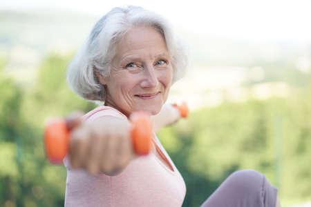 Portrait of smiling senior woman with white hair doing fitness exercises outside