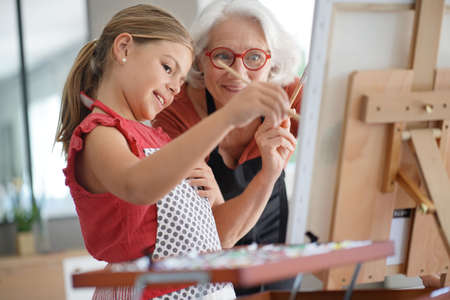 Young girl with grandmother painting on canvas 스톡 콘텐츠