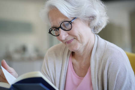 Senior woman relaxing in armchair and reading book 스톡 콘텐츠