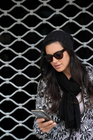 Portrait of trendy woman with dark hair and sunglasses, standing on iron curtain and using smartphone