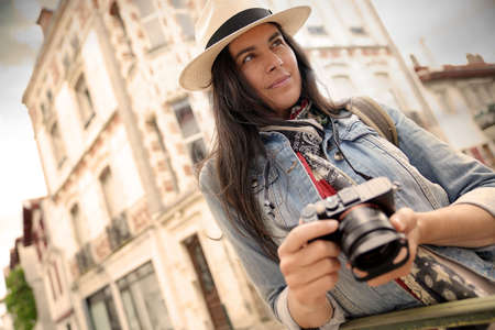 Woman wearing hat, taking pictures in european town during vacation 스톡 콘텐츠