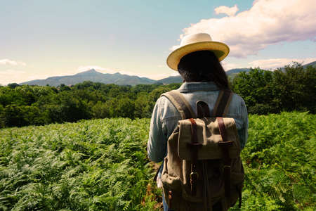 Woman with backpack on a journey in coutryside, wearing hat 스톡 콘텐츠
