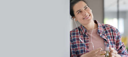 Beautiful 40-year-old woman at home with earphones on, drinking herbal tea -template