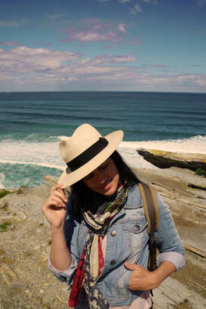 Woman with hat on relaxing by the ocean coast 스톡 콘텐츠