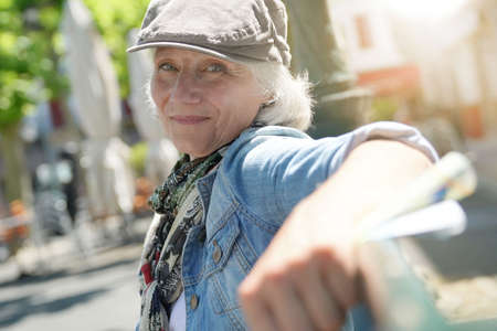 Trendy senior woman with hat relaxing on public bench in small town
