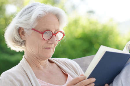 Senior woman with red eyeglasses reading book outside