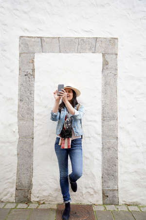 Woman wearing blue jeans and hat, standing against wall and using smartphone