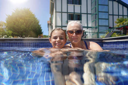Grandmother with grandkid in resort swimming-pool