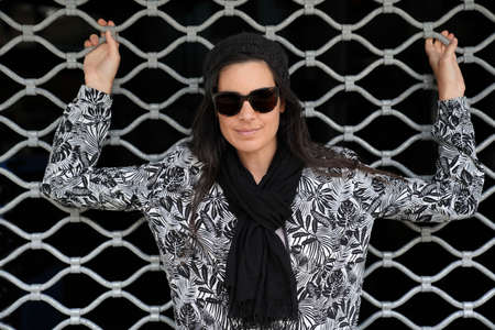 Portrait of trendy woman with dark hair and sunglasses, standing on black curtain