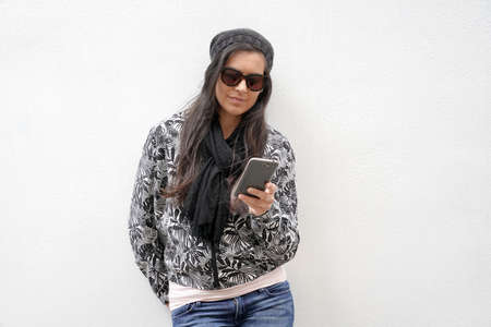 trendy woman wearing black sunglasses standing on concrete wall and using smartphone 스톡 콘텐츠 - 151472556