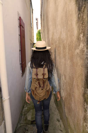 Tourist woman walking in narrow streets of small town