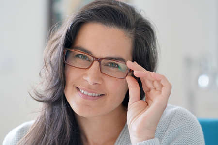 Portrait of beautiful 40-year-old woman with long dark hair wearing eyeglasses