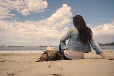 Back view of woman looking at the sea from the beach