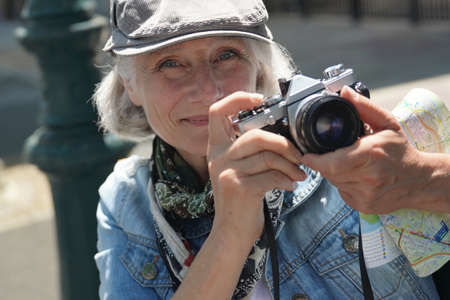 Portrait of senior woman on a journey in touristic area taking picture with vintage camera 스톡 콘텐츠