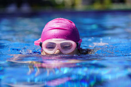 Young girl training in outdoor swimming-pool 스톡 콘텐츠