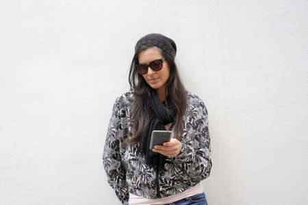 trendy woman wearing black sunglasses standing on concrete wall and using smartphone