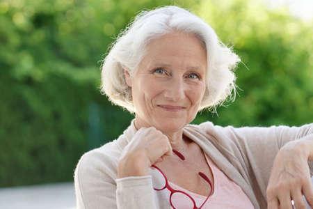 Portrait of senior woman relaxing in armchair outside