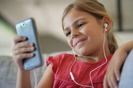 Young girl connected with smartphone and earphones 스톡 콘텐츠