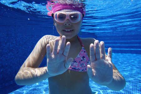 Young girl swimming underwater in blue pool