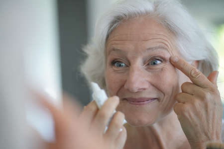 Portrait of senior woman taking care of her skin, looking at mirror 스톡 콘텐츠