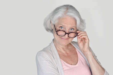 Portrait of senior woman with eyeglasses standing on white background, isolated
