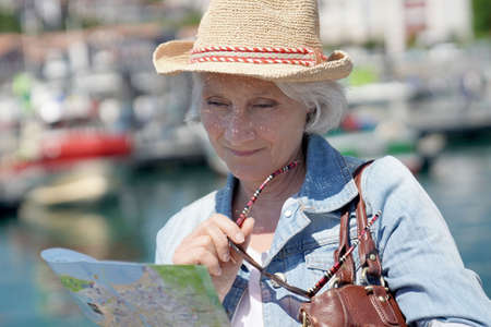 Portrait of senior woman with hat visiting touristic town, reading city map