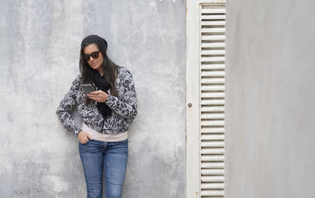 trendy woman wearing black sunglasses standing on concrete wall and using smartphone 스톡 콘텐츠 - 151814540