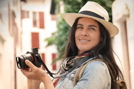 Woman visiting town taking pictures of architectural details with reflex camera