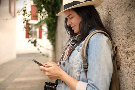 Woman tourist with dark hair leaning on wall in the street, connected with smartphone 스톡 콘텐츠