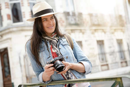 Woman wearing hat, taking pictures in european town during vacation 스톡 콘텐츠 - 151814614