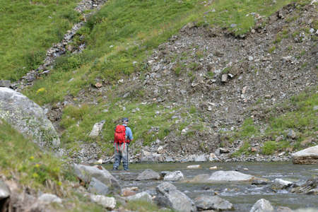 fly fisherman trout fishing with a hiking backpack and a blue shirt in the high mountains in summer