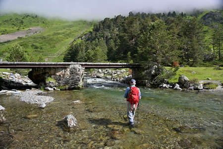 fly fisherman trout fishing with a hiking backpack and a blue shirt in the high mountains in summer 스톡 콘텐츠 - 151814620