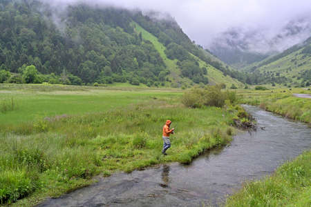 fly fisherman with an orange jacket fishing for trout in the mountains in rainy weather 스톡 콘텐츠