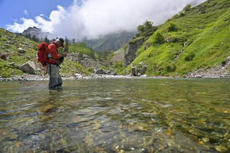 fly fisherman trout fishing with a hiking backpack with an orange jacket in the high mountains in summer