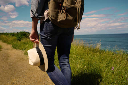 Woman walking by the ocean coast, holding hat and carrying backpack 스톡 콘텐츠