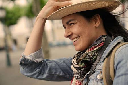 Portrait of happy dark-haired woman wearing hat