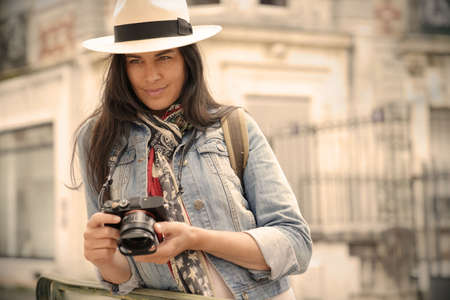 Woman wearing hat, taking pictures in european town during vacation Stock fotó
