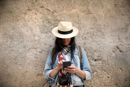 Woman wearing blue jeans and hat, standing against wall and using smartphone Reklamní fotografie - 151814903