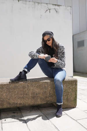trendy girl with sunglasses, sitting on concrete bench and using smartphone
