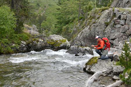 fly fisherman trout fishing with a hiking backpack and an orange jacket in the high mountains in summer