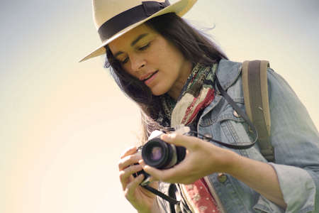Portrait of dark-haired woman with hat taking pictures with vintage camera Stock fotó