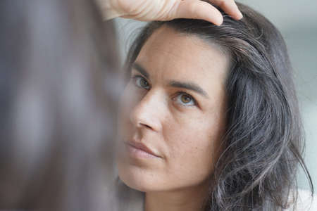 Middle-aged woman checking hair roots in front of mirror Stock fotó