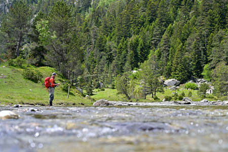 fly fisherman with a red backpack and a red jacket fishing in a high mountain river in summer