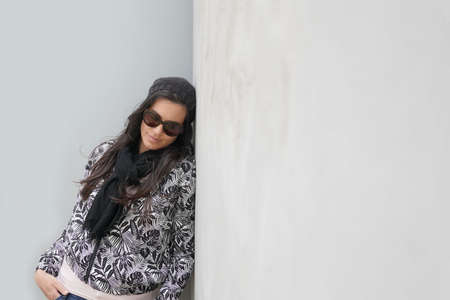 trendy woman wearing black sunglasses and scarf standing on concrete wall, isolated 스톡 콘텐츠 - 151814941