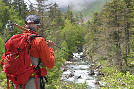 fly fisherman fishing for trout on a hike with a backpack and an orange jacket in the high mountains in summer
