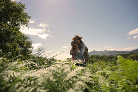 Woman with hat taking pictures in beautiful and natural landscape Stock fotó
