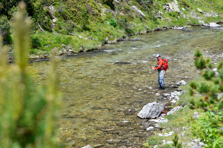 fly fisherman trout fishing with a hiking backpack and an orange jacket in the high mountains in summer 스톡 콘텐츠 - 151815041
